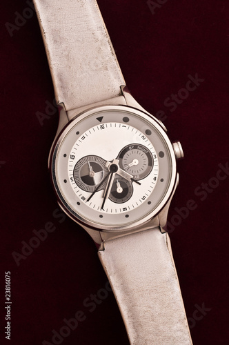 used silver watch isolated over a dark red backgtound