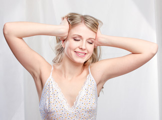 Pretty blond woman waking up and stretching arms