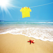 Yellow T shirt hung on a line on beach