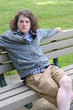 Young adult relaxes on bench