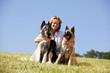 hübsche blonde Frau mit zwei belgischen Schäferhunden