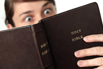 Young woman reading the Bible with surprised look