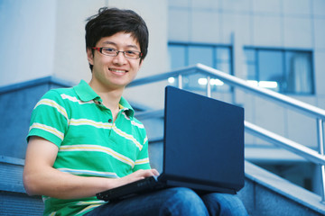 asian male student with laptop
