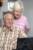 Senior couple brows Internet on their laptop. poster