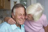 Senior couple shares tender moment in their kitchen. poster