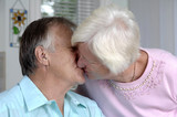 Senior couple shares some tender moments in their kitchen. poster