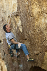 Rock climber clinging to steep cliff.