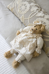 teddy bear in dress lying on the bed