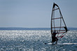 windsurfer silhouette against a sparking blue sea