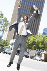 Businessman jumping at street