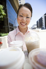 Portrait of young woman with take-away coffees  outdoors
