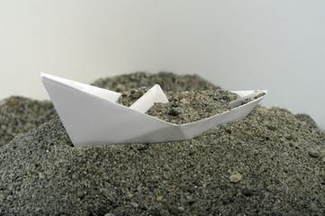 Barca di carta nella sabbia