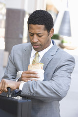Businessman eating sandwich and checking time