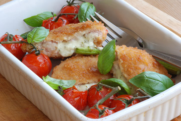 Chicken kievs with cooked tomatoes and basil