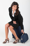 Young woman sitting on luggages