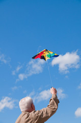 Senior man flying kite