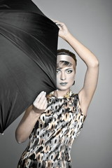 Beautiful fashion girl on the grey background with umbrella