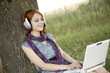Young smiling fashion girl with notebook and headphones sitting