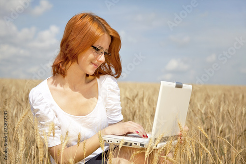 Young Businesswomen in white working with notebook at wheat fiel