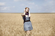 Young  smiling fashion with headphones at wheat field.
