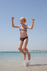little girl jumping over the water