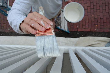 Painter Applying Paint to Exterior Balusters of Home