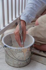House Painter Dipping Brush in Pail