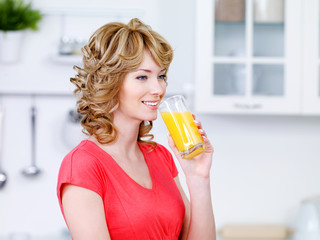 Woman drinking juice in the kitchen