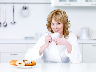 Woman sitting in the kitchen and drinking coffee