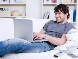 Guy typing on the laptop at home
