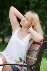 Pretty  blond woman sits with raised arms on park bench