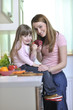 happy daughter and mom in kitchen