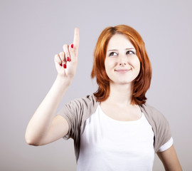 Red-haired businesswoman show her finger on something in air.