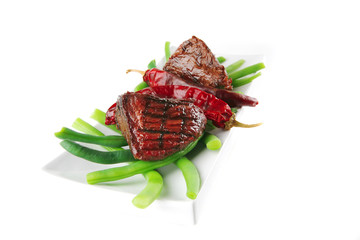 fillet mignon on a white plate and peppers