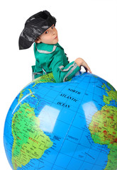 boy in historical dress leans on inflatable globe isolated