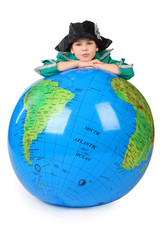 boy in historical dress leans on inflatable globe chin on hands