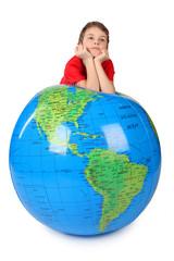 boy in red shirt leans on inflatable globe chin on hands