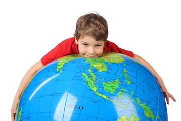 boy in red shirt lies on inflatable globe isolated on white
