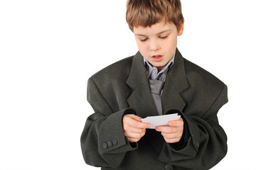 little boy in big grey man's suit looking at  business card