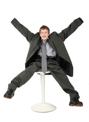little boy in big grey man's suit sitting on chair and smiling