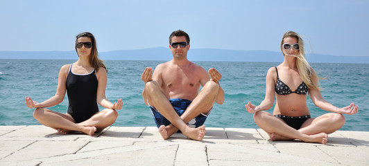 Young students practising yoga on the beach