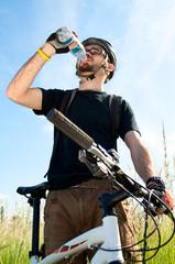 closeup of a young biker drinking water