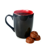 coffee is in a black cup and chocolate candies
