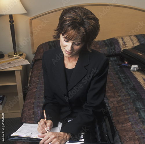 Businesswoman Fills Out Forms In Hotel Bedroom