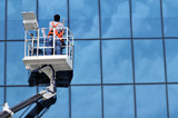 Window washing on high-rise office building in crane beam