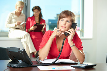 Businesswoman talking on landline phone