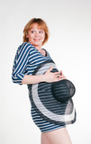 Funny pregnant woman covering her belly with a hat