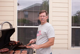 Young man barbecuing hamburgers and sausages