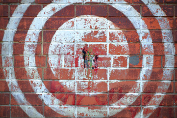 Painted target on a red brick wall.