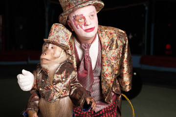Circus clown with a monkey.